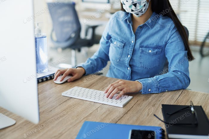 Unrecognizable person in face mask working in the office