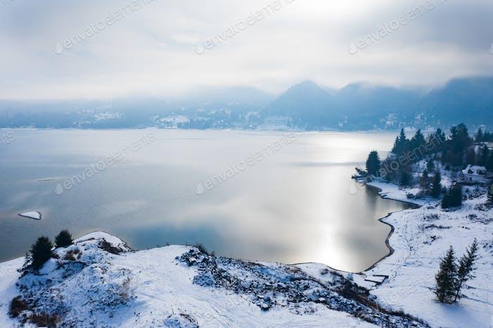 Magic foggy sunrise over Colibita lake in winter, Romania.