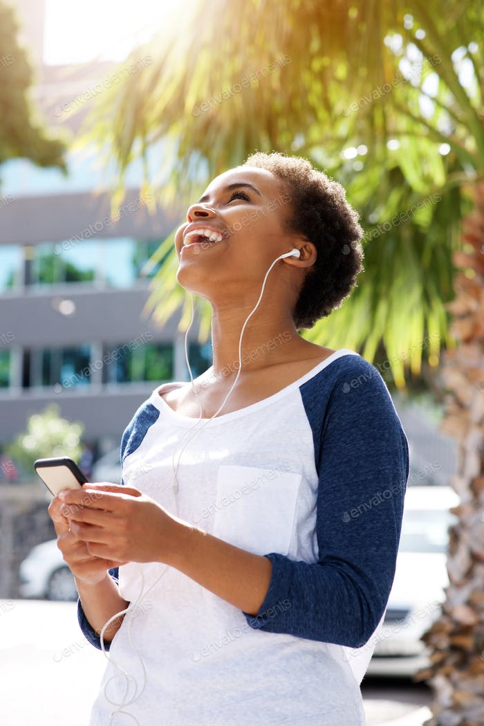 happy young black woman listening to music on cellphone