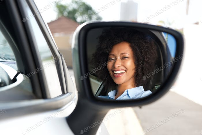 reflection in side mirror of smiling african woman driving car
