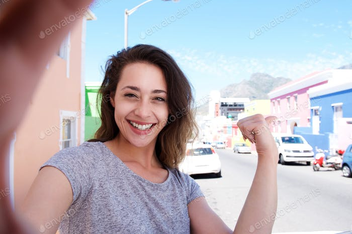 smiling young woman taking selfie outside