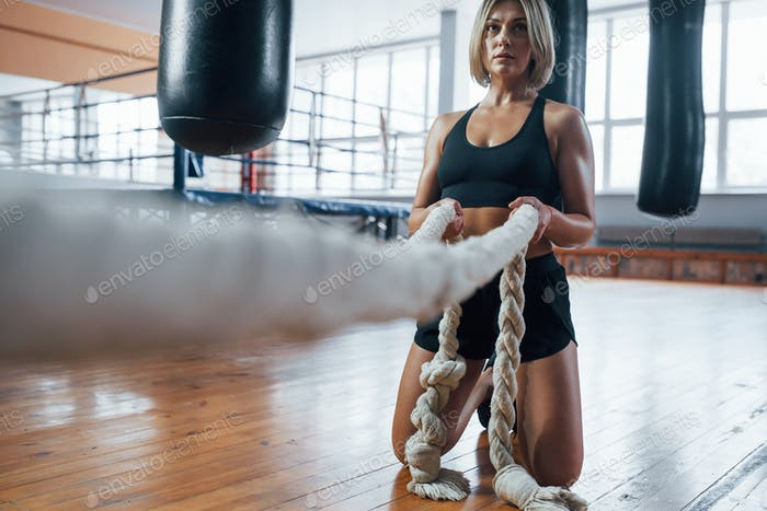 Physical routine. Blonde sport woman have exercise with ropes in the gym. Strong female