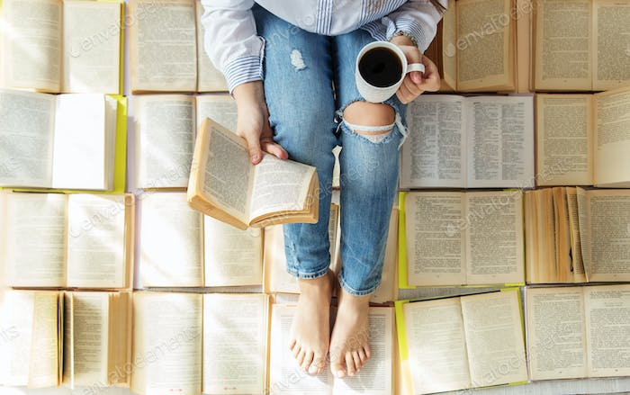 A young woman reads a book and drinks coffee. A lot of books. Concept for World Book Day