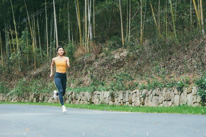 Junge asiatische Frau läuft in der Landstraße