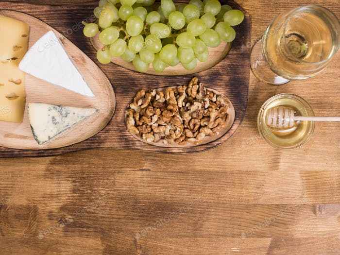 Top view of white wine served with honey on wooden table