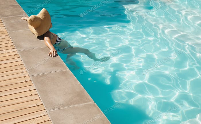 Young woman with big sun hat leaning on edge of pool in  backyard of her home