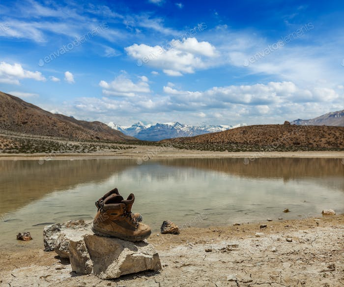 Trekking hiking boots at mountain lake in Himalayas