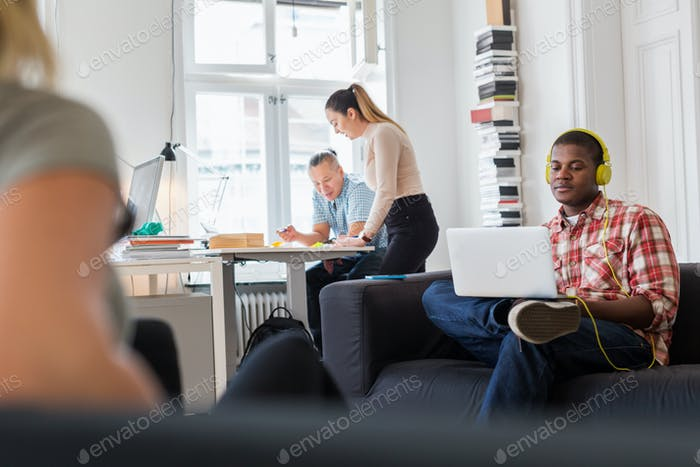 Worker using laptop on sofa and listening music, colleagues working in background
