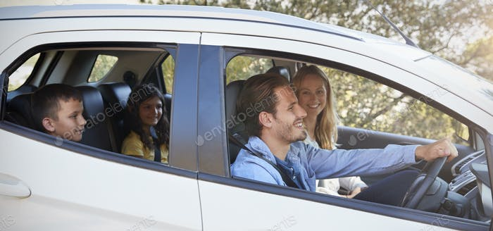 Happy young family with two children driving in their car
