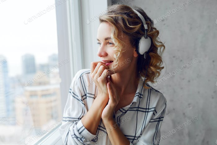 Indoor lifestyle portrait of cheerful  successful woman listening to music
