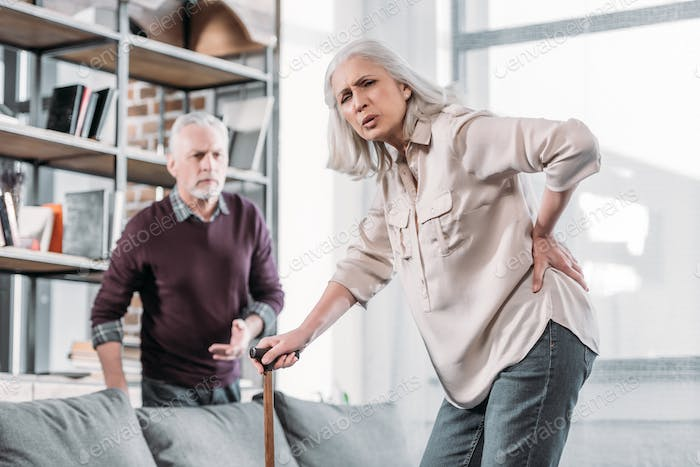 senior woman suffering from strong back pain at home