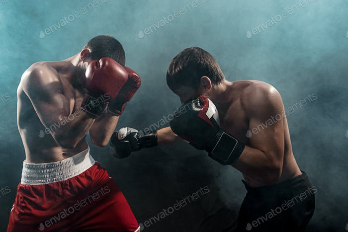 Two professional boxer boxing on black smoky background,