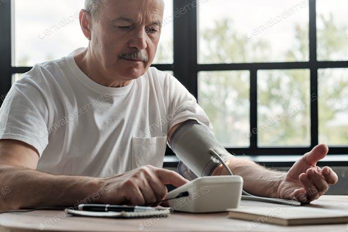 Mann, der einen Blutdruck am Morgen überprüft
