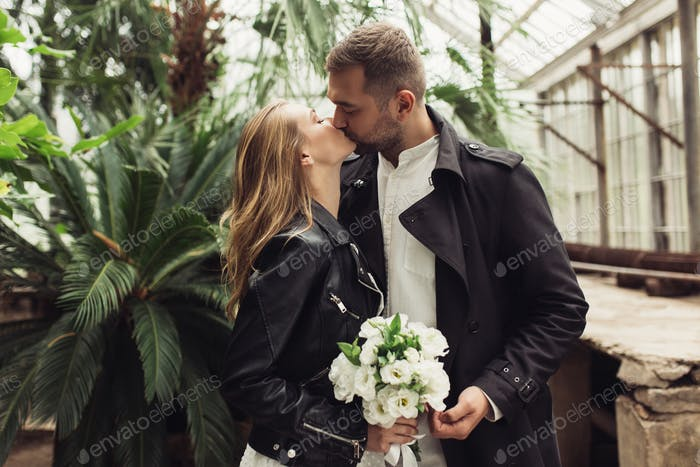 Young handsome man kissing beautiful woman in black leather jack