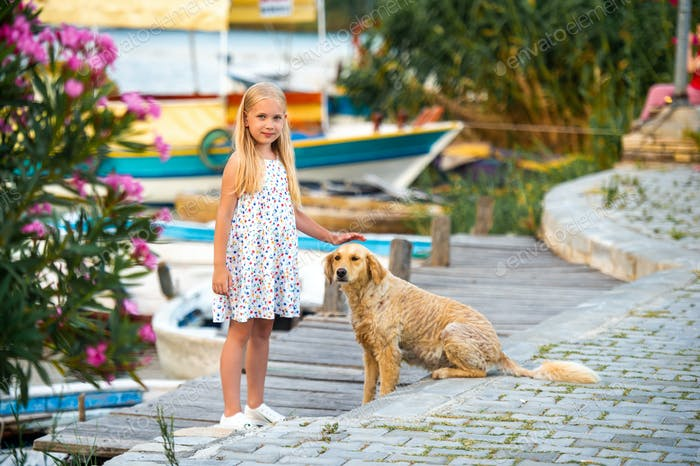 A little girl with a dog on the embankment by the river in a white sundress in the city of Dalyan