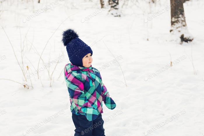 Little girl in winter clothes in snow forest at snowflakes background