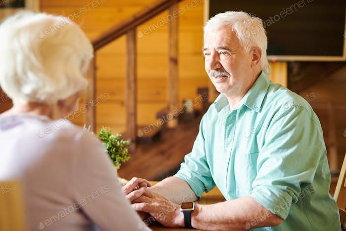Amorous senior man looking at his wife during conversation