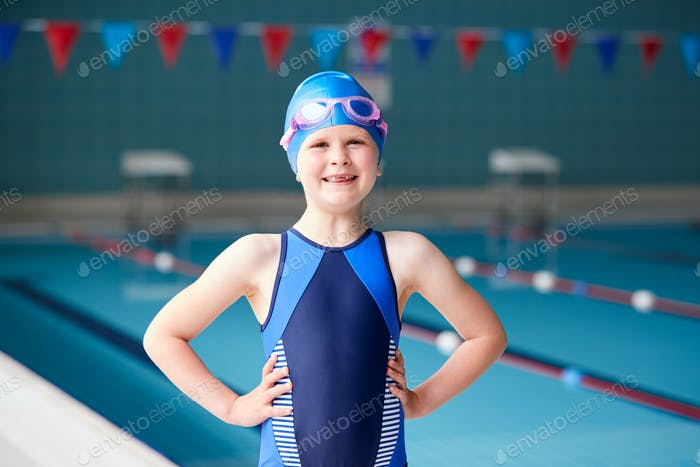Portrait Of Girl Standing By Edge Of Swimming Pool Ready For Lesson