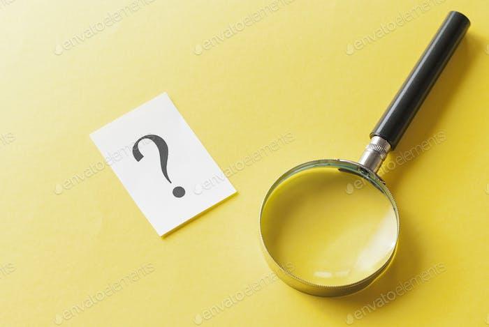 Lupa con signo de interrogación impreso