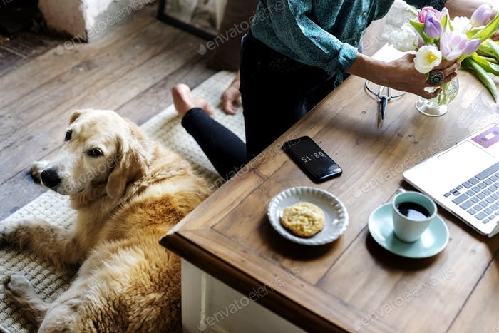 Woman Arranging Flowers with Goldent Retriever Dog Laying