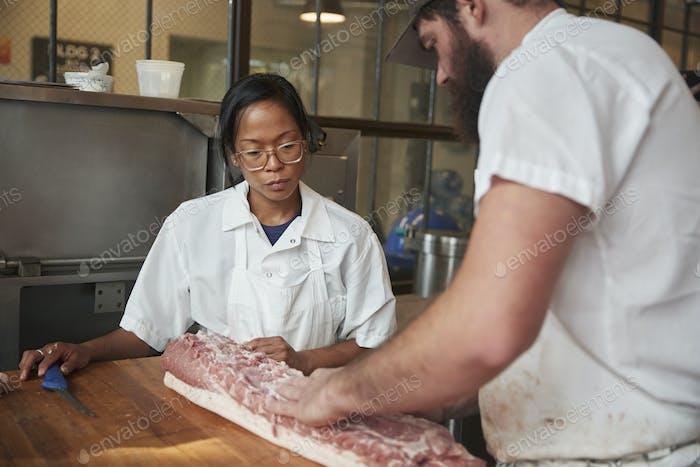 Mann und Frau, die Fleisch zubereiten, Fleischstücke in einer Metzgerei zu verkaufen