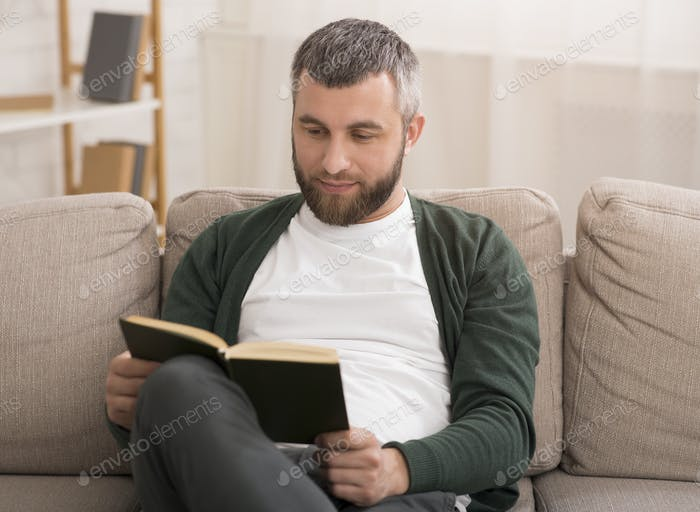 Handsome middle aged man reading book at home