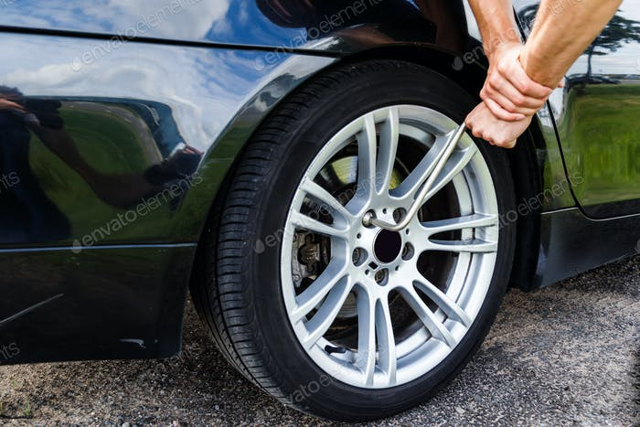man unscrews bolts of the rear wheel the car to change the tires.