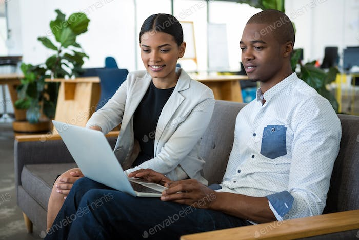 Businessman and a colleague discussing over laptop