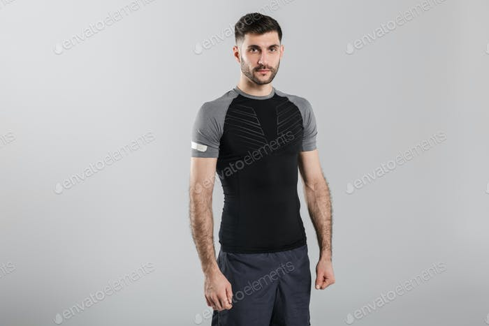Bild des jungen starken Mannes in Sportbekleidung posiert und Blick auf die Kamera