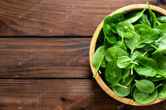 Fresh spinach leaves on wooden background. Healthy vegan food. Top view