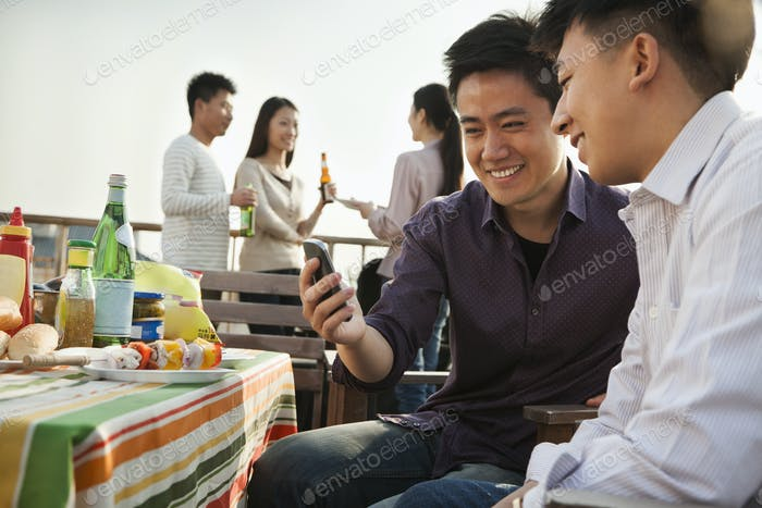 Friends Using Cell Phone at Rooftop Barbecue