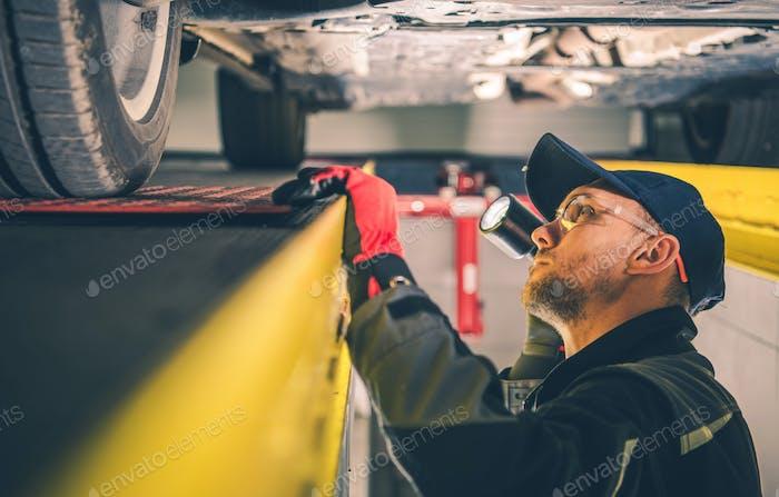Car Mechanic Spotting Vehicle Suspension Problems