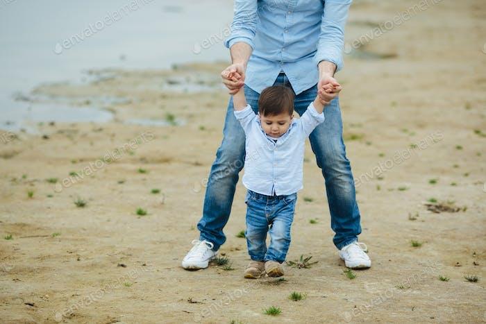 Papa hält Säuglingssohn Hände