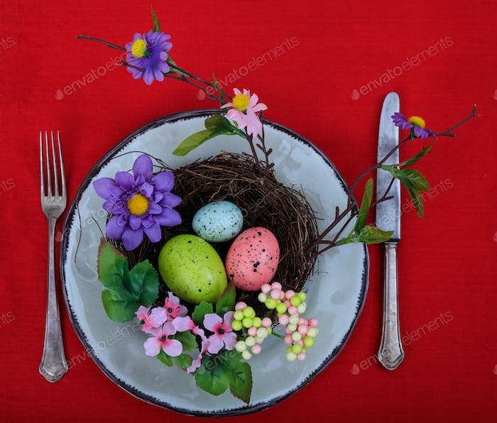Easter decoration on a plate on red tablecloth