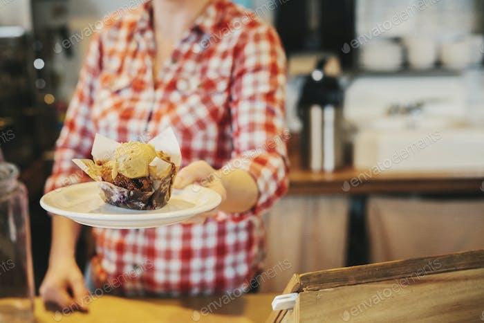 Eine Frau in einem Café hält einen Teller mit einem frischen Muffin mit einer Schaufel Eis.