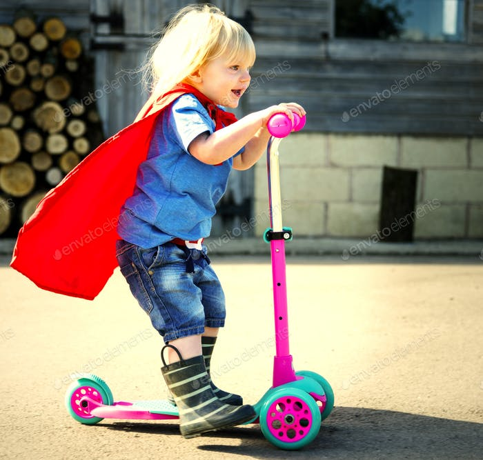 Happy little boy playing superhero with imagination