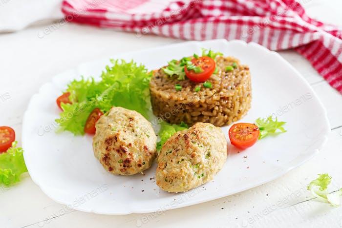 Hausgemachte gebackene Schnitzel mit Reis auf einem Tisch im rustikalen Stil. Gesunde Ernährung