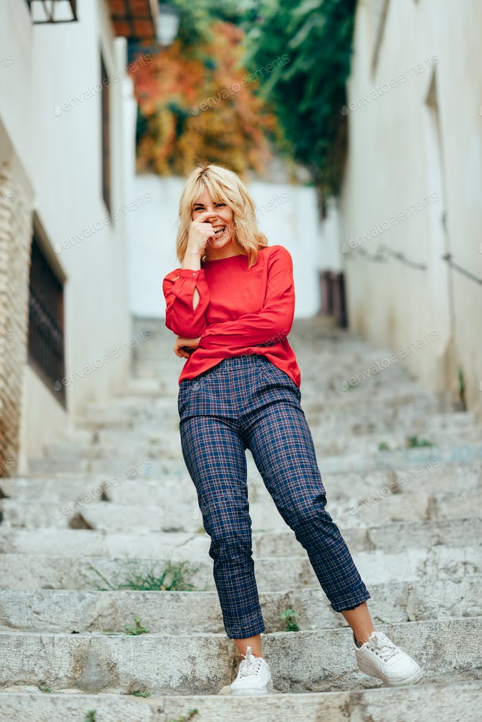 Happy young blond woman laughing on beautiful steps in the street.