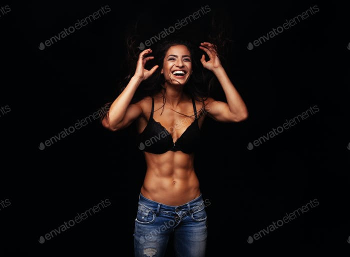 Cheerful young woman in bra and jeans