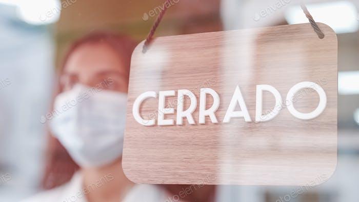 Junge traurige Frau mit Gesichtsmaske wechselt aufgeschlossen auf Spanisch auf Fenster für Coronavirus