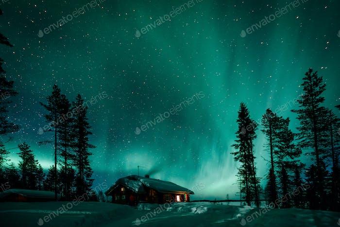 Nordlichter Aurora Borealis Aktivität über Holzhütten im Winter Finnland