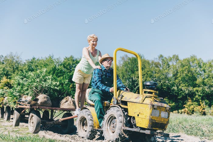 Older couple riding on tractor trailer