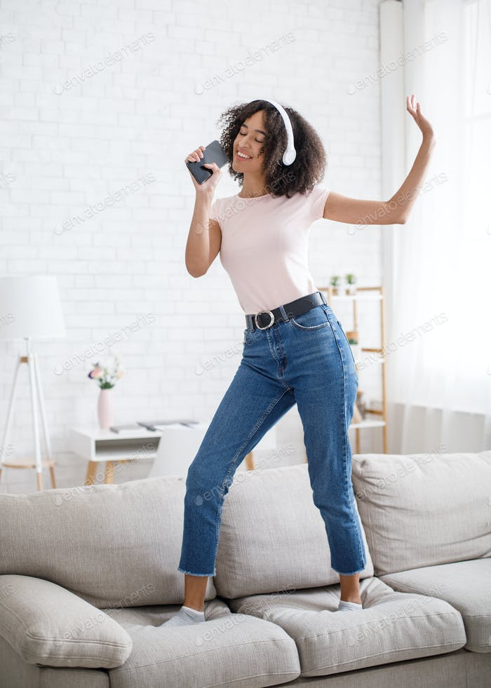 Musical mobile app and imaginary microphone. Funny african american woman dancing on sofa