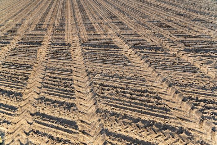 Plowed field brown soil tractor tracks
