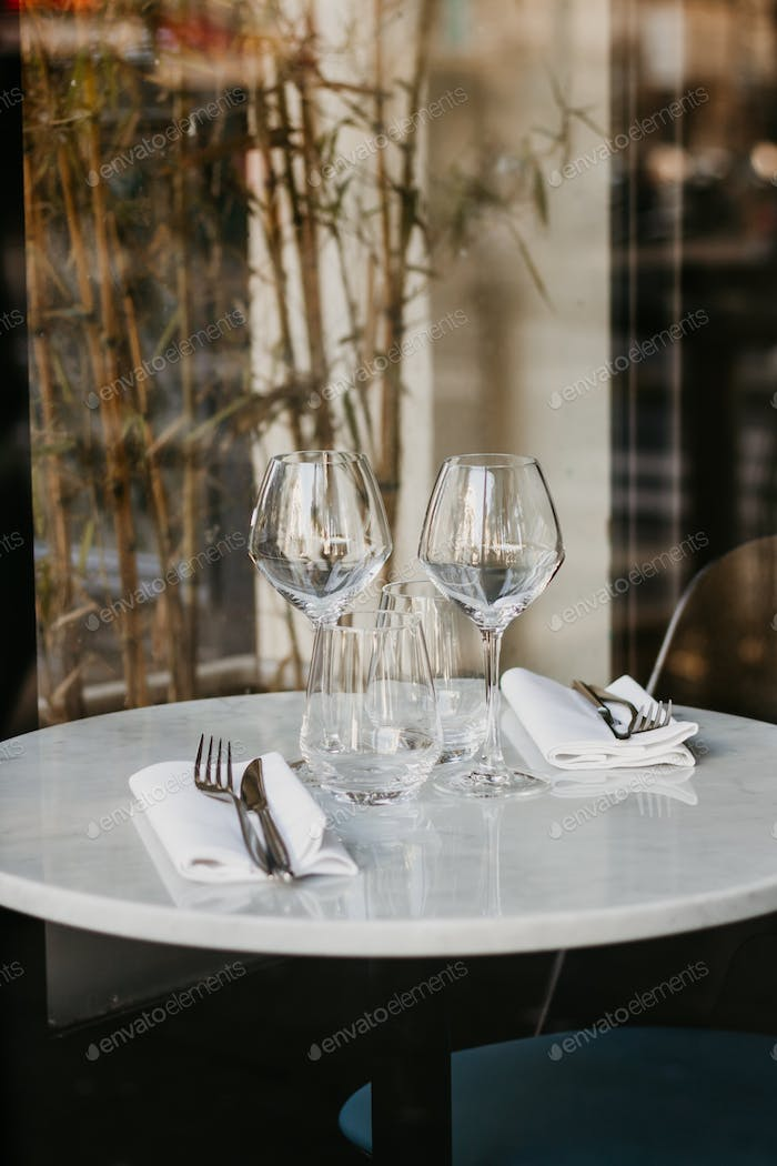 Table setting in a French restaurant for two. View through a window from a street.