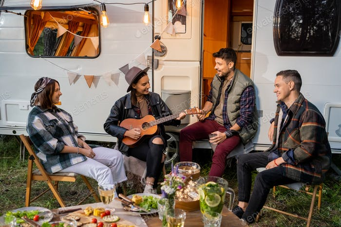 Group of happy young friends singing songs by house on wheels