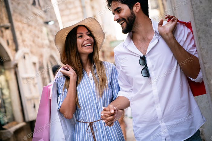 We love shopping together. Beautiful young loving couple walking by the street