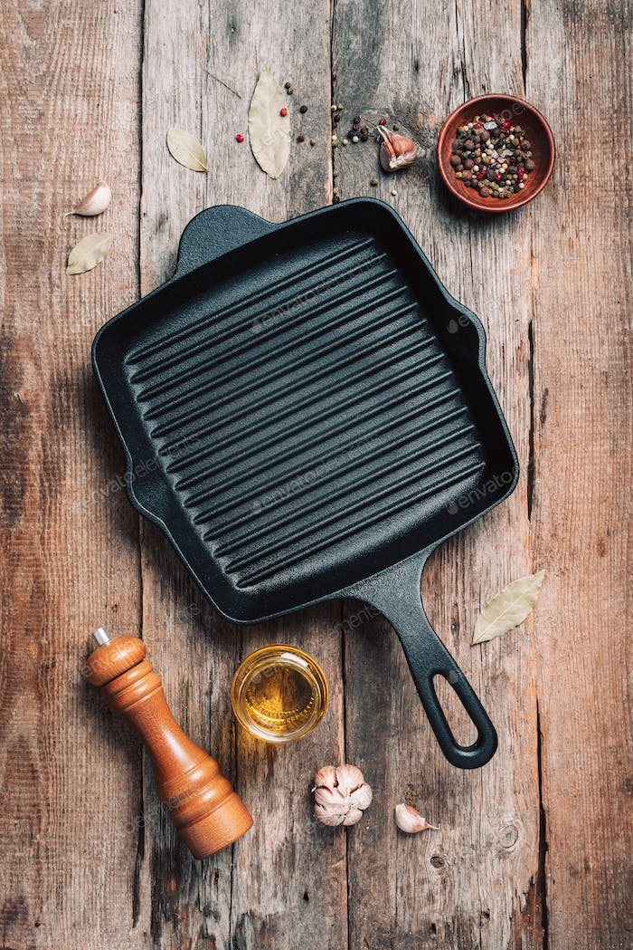 Empty grill iron pan and kitchen utensils on wooden background. Top view. Copy space. Healthy, clean