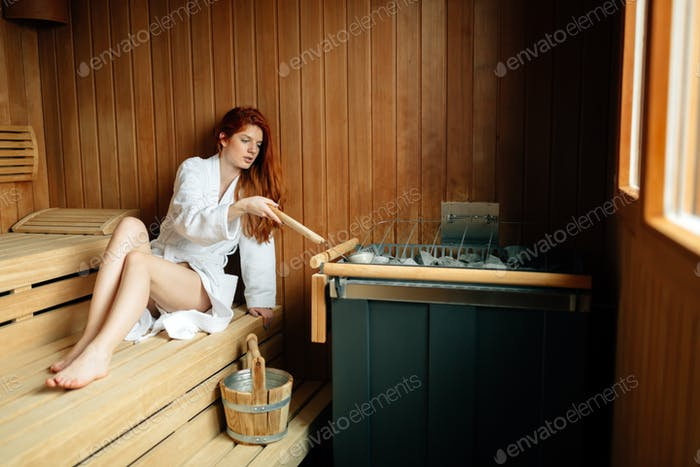 Beautiful woman in sauna pouring oils on hot stones