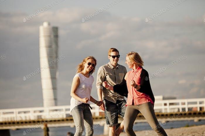 Fröhliche Freunde genießen am Strand gegen Turning Torso im Sommer